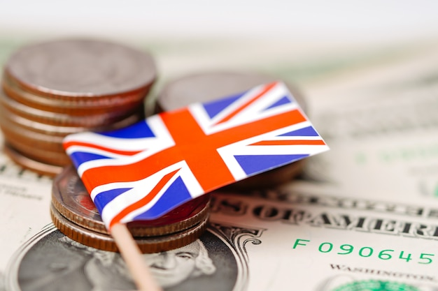 England flag with coins on dollar banknotes background.