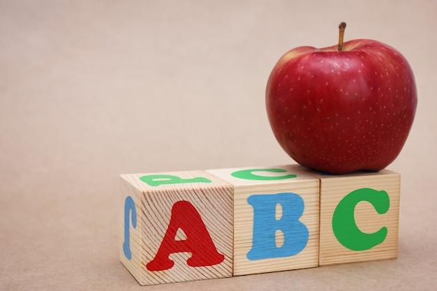 英語のabcアルファベットとその上の赤い新鮮なリンゴ。教育の概念。