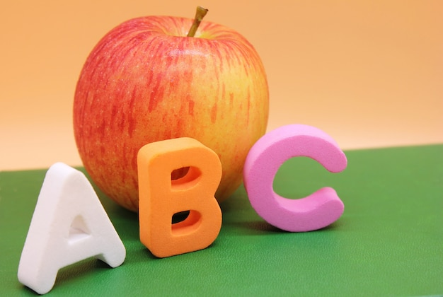 English abc alphabet letters next to book and apple.