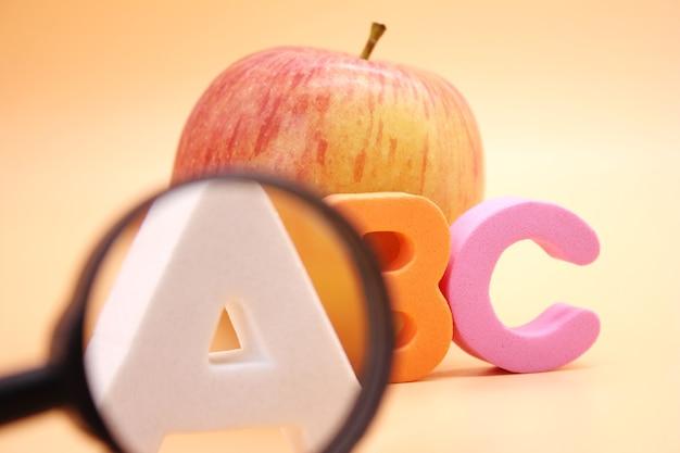 リンゴと拡大鏡の横にある英語のabcアルファベット。外国語を学ぶ。