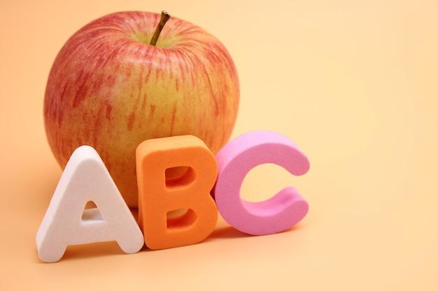 リンゴの横にある英語のabcアルファベット。外国語を学ぶ。