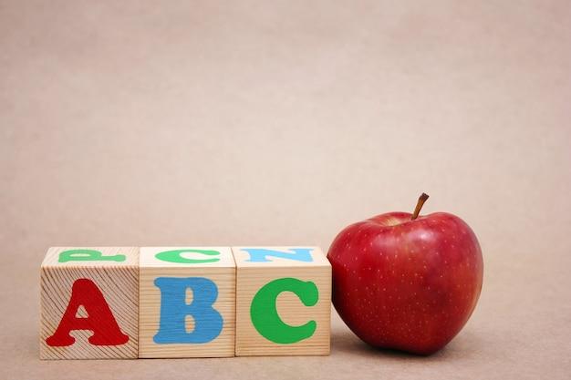 赤いリンゴの横にある英語のabcアルファベット。外国語を学ぶ。