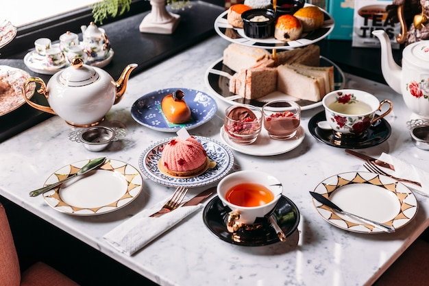 English afternoon tea set including hot tea, pastry, scones, sandwiches and mini pies.