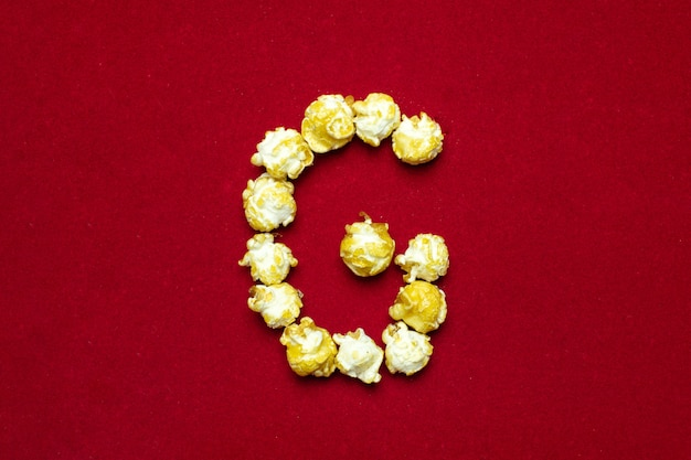 English alphabet from cinema popcorn. letter g. red background for design