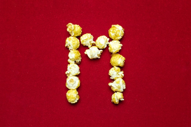 English alphabet from cinema popcorn. letter m. red background for design