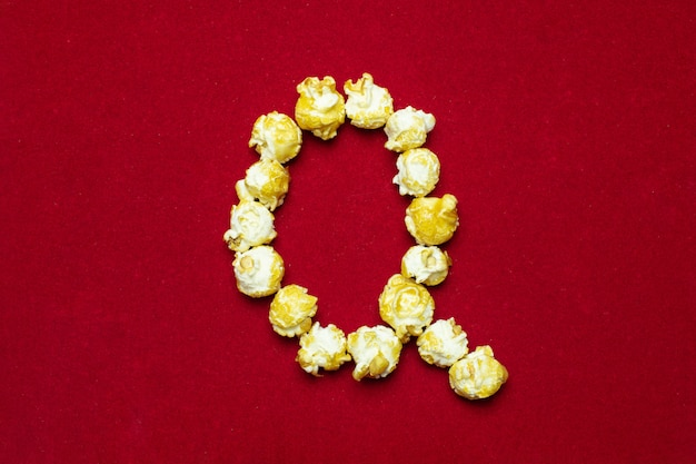 English alphabet from cinema popcorn. letter q. red background for design