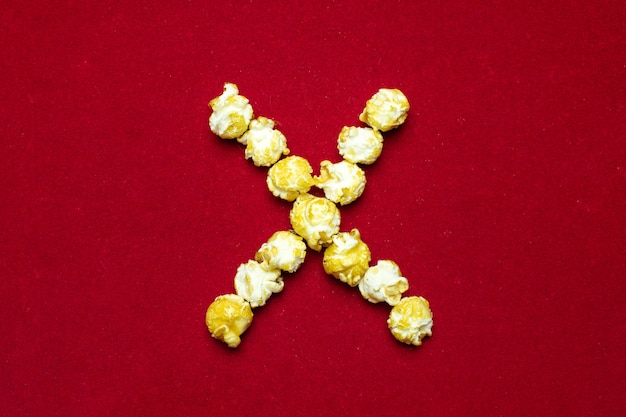 English alphabet from cinema popcorn. letter x. red background for design