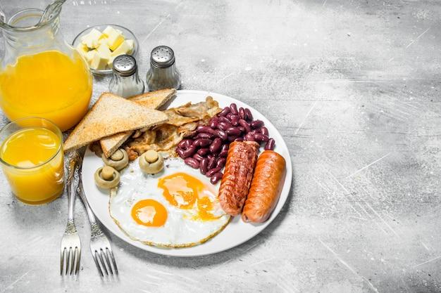 영국식 아침 식사. 오렌지 주스와 함께 다양한 간식. 소박한 배경.