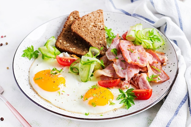 Английский завтрак - яичница, бекон, помидоры и хлеб.