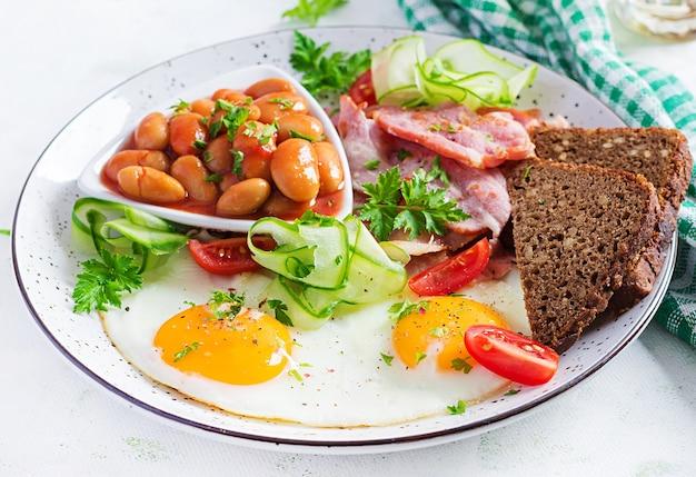 Английский завтрак - яичница, фасоль, бекон, помидоры и хлеб.