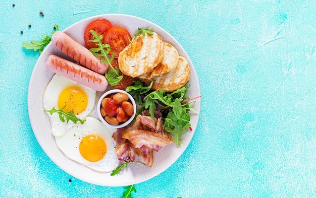 Английский завтрак - жареное яйцо, фасоль, помидоры, колбаса, бекон и тосты.