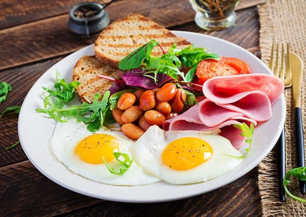 Английский завтрак - жареное яйцо, фасоль, помидоры, колбаса, ветчина и тосты.