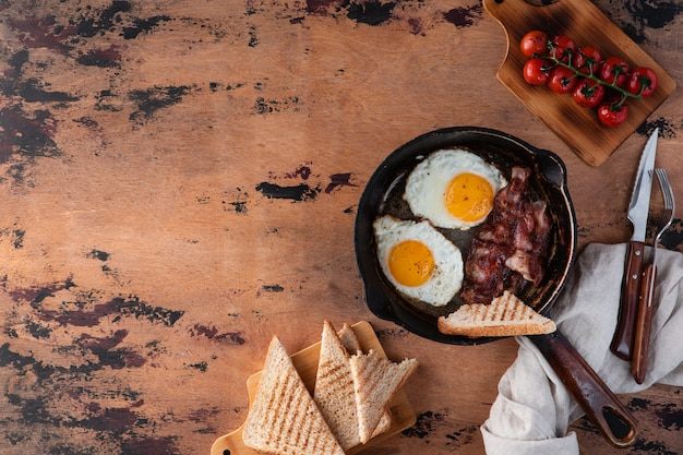 English breakfast of fried egg, tomatoes, bacon and toast.