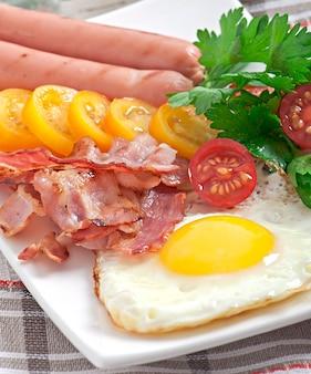 Английский завтрак - яичница, бекон, сосиски и поджаренный ржаной хлеб