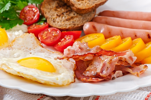 English breakfast - fried eggs, bacon, sausages and toasted rye bread