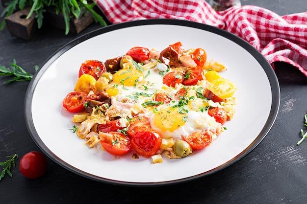 Английский завтрак - яичница, ветчина, помидоры и руккола. американская еда.