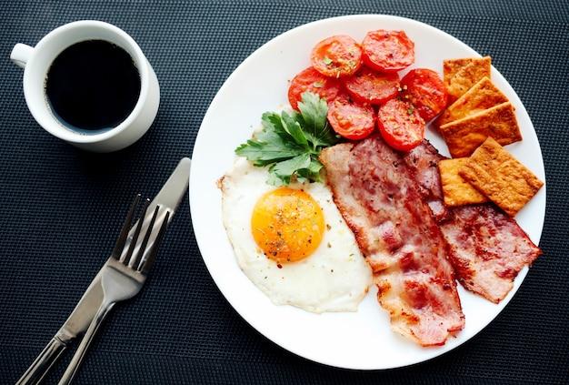 Английский завтрак - яичница, зелень, помидоры, бекон и крекеры