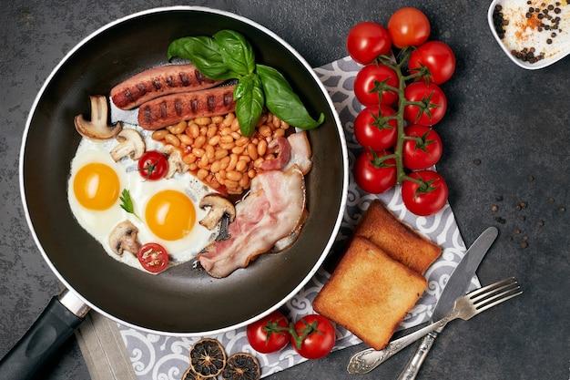 Английский завтрак. жареные яйца, сосиски, бекон, фасоль, тосты, помидоры на каменном столе. вид сверху с копией пространства