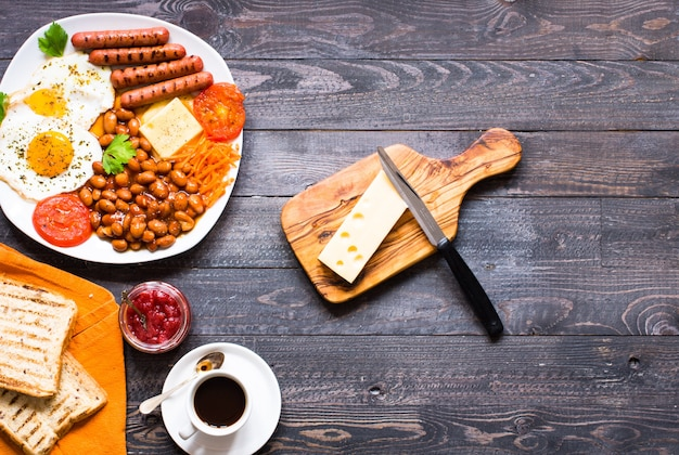 English breakfast. fried eggs sausages beans bread toasts tomatoes cheese on a wooden background
