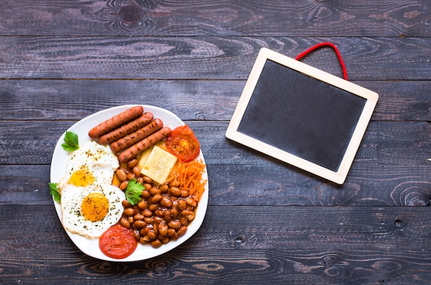English breakfast. fried eggs, sausages, beans, bread toasts, tomatoes, cheese on a wooden surface,
