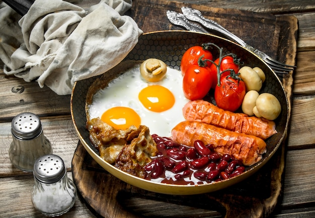 イングリッシュブレックファースト。ソーセージと目玉焼き、木製のテーブルにベーコンドの赤い缶詰の豆。