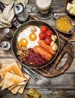 イングリッシュブレックファースト。素朴なテーブルにソーセージ、フライドブレッド、アロマコーヒーを添えた目玉焼き。