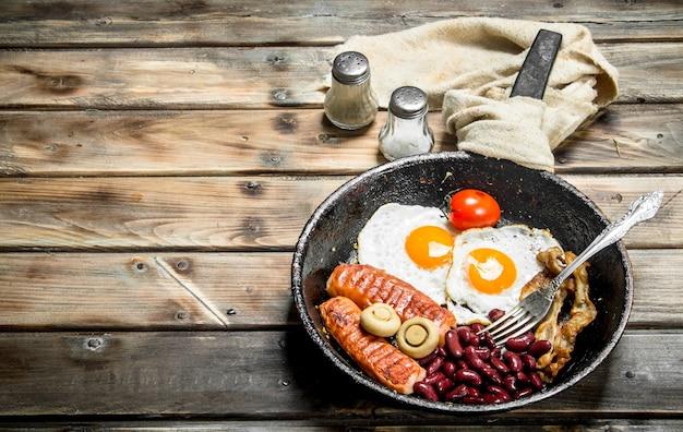 イングリッシュブレックファースト。トマト、ソーセージ、豆と目玉焼き。木製のテーブルの上。