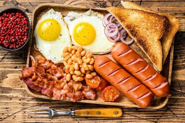 달걀 프라이, 소시지, 베이컨, 콩, 토스트가 들어간 나무 쟁반에 담긴 영국식 아침 식사. 나무 배경입니다. 평면도.