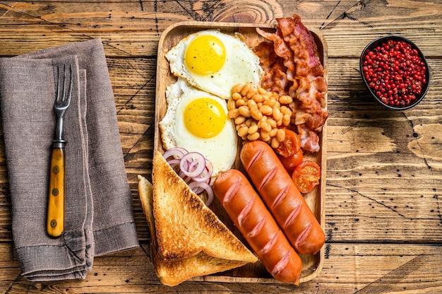 Английский завтрак на деревянном подносе с яичницей, сосисками, беконом, фасолью и тостами. деревянный стол. вид сверху.