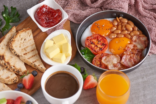튀긴 계란, 베이컨, 콩, 구운 토마토와 함께 냄비 요리에 영국식 아침 식사.
