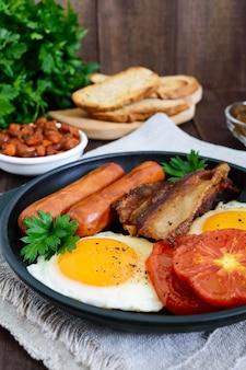 영국식 아침 식사 : 소시지, 베이컨, 토마토, 계란, 소스에 콩, 튀긴 버섯, 어두운 나무 테이블에 토스트. 세로보기. 영국의 전통 음식.