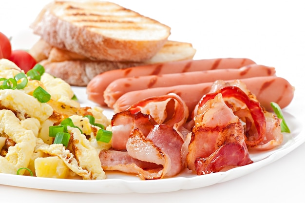 English breakfast - scrambled eggs, bacon, sausage and toast