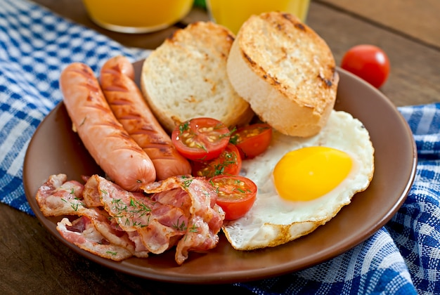 English breakfast - toast, egg, bacon and vegetables in a rustic style on wooden surface