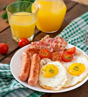 Colazione inglese - toast, uova, pancetta e verdure in stile rustico sul tavolo di legno