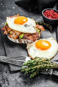 Английский завтрак, тост с беконом, авокадо и яйцом на разделочной доске. здоровая пища. черный фон. вид сверху.