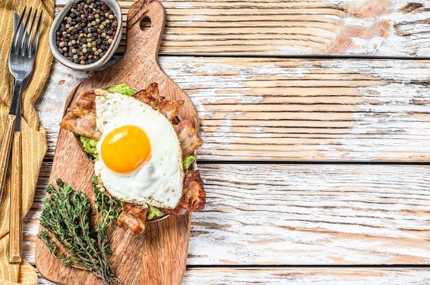 イングリッシュブレックファスト、まな板の上にベーコン、アボカド、卵とトースト。