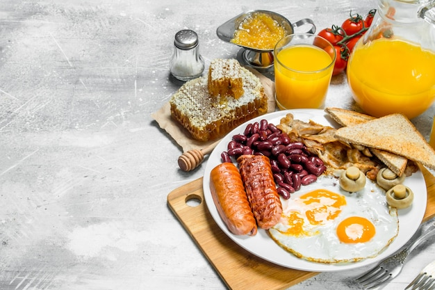 English breakfast. a variety of snacks with orange juice. on a rustic surface.