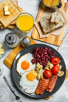English breakfast. a variety of snacks with orange juice on a rustic table.