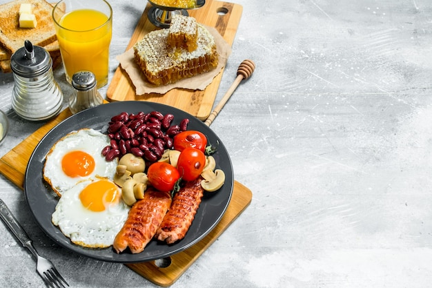 English breakfast. a variety of snacks with orange juice. on a rustic table.
