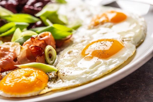 Английский завтрак с яйцами, беконом, фасолью и молодым луком в белой тарелке.