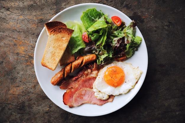 目玉焼き、ハム、ソーセージ、ベーコン、サラダ、トーストを白いプレートに載せたイングリッシュブレックファースト