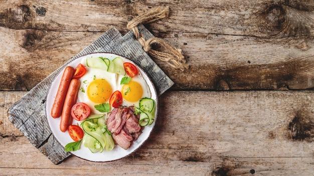 Английский завтрак с яичницей, беконом, сосисками и свежим салатом