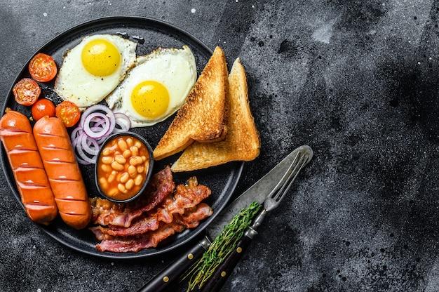 튀긴 계란, 소시지, 베이컨, 콩, 토스트가 접시에 담긴 영국식 아침 식사. 검정색 배경. 평면도. 공간을 복사하십시오.