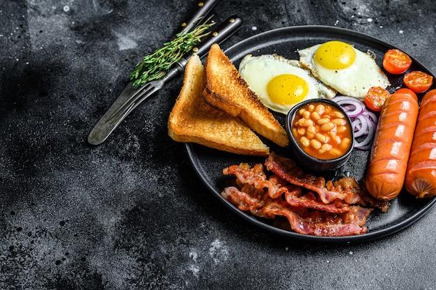 Английский завтрак с яичницей, сосисками, беконом, фасолью и тостами в тарелке. вид сверху.