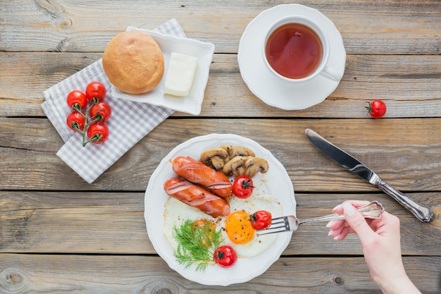 English breakfast with fried eggs, sausages, mushrooms, grilled tomatoes and cup of tea on rustic wooden table. top view