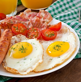 English breakfast with toast, egg, bacon and vegetables in a rustic style on wooden table