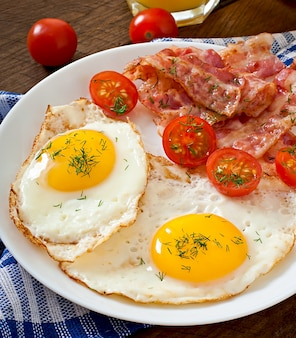 English breakfast with toast, egg, bacon and vegetables in a rustic style on wooden