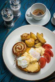 木製のテーブルにトースト、ポーチドエッグ、ソース、ソーセージを添えたイングリッシュブレックファースト