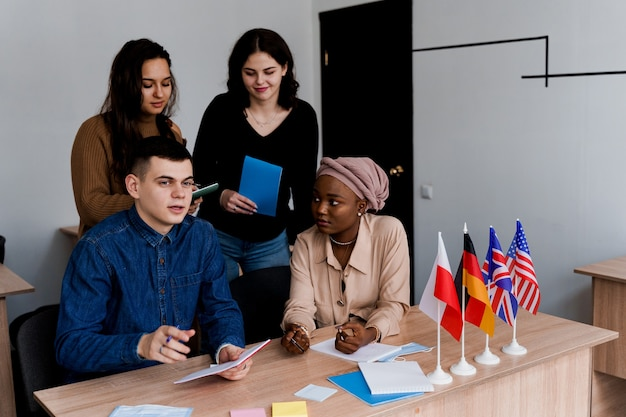 English class study with students from different countries: poland, germany, usa. teamwork. working in multiethnic students. teacher study foreign languages together in class. studying with laptop.