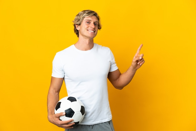 English football player over isolated yellow background showing and lifting a finger in sign of the best